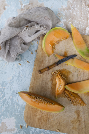 scraped: fresh melon slices with seed on chopping board on rustic background with scraped wood and knife
