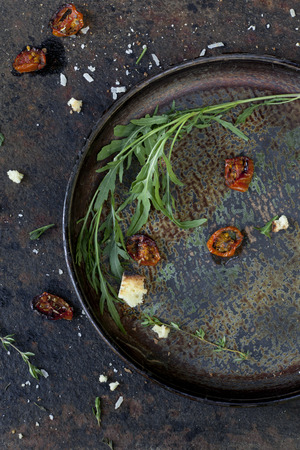 scraped: composition on vintage scraped tray with backed cherry tomatoes and wild rocket leaves