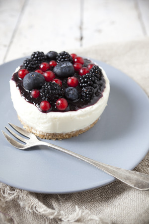whole mini cheesecake with blackberries, blueberries and red currant on plate with fork photo