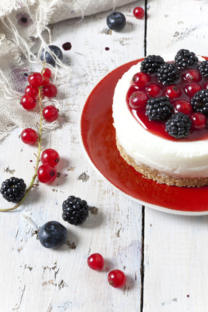 whole mini cheesecake with blackberries, blueberries and red currant on plate and berries on wooden white table photo