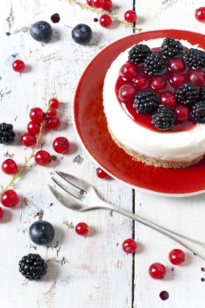 whole mini cheesecake with blackberries, blueberries and red currant on plate with fork and berries on wooden white table photo