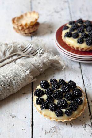 pic nic: two homemade blackberries tart with pastry cream on wooden table with cloth, fork and little plate with tart waffles