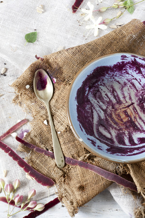 eaten purple carrot cream soup on bowl on rustic vintage background with carrot peels and burlap photo