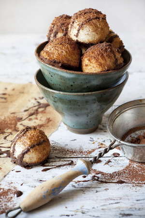 homemade coconut macaroons with dripped dark chocolate and cocoa powder on bowl with chocolate backdrop and vintage strainer photo