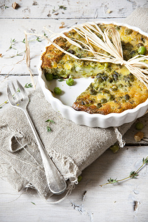 rustic vegetables french quiche with peas on baking dish on vintage background on wooden table with fork and burlap photo