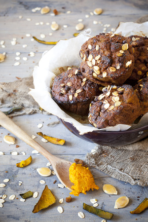 chocolate dessert: homemade rustic muffins with pumpkin chocolate and oat flakes on bowl with burnt greasproof paper on vintage background