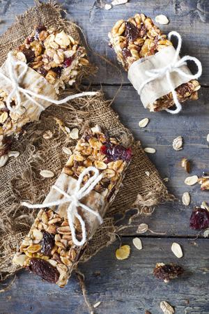 barra de cereal: barras de granola caseras r�sticas con frutas y hecho a mano pasas envasadas en fondo de la vendimia de madera azul