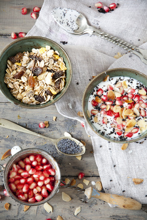 strainer: pomegranate grains on vintage strainer and two bowl of natural yogurt with seed, grains, cereals and muesli with spoon on rustic table