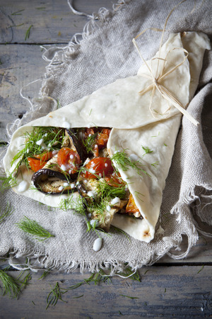 vegetarian flatbread roll with grilled eggplants, roasted tomatos, wild fennel herb and seed with yogurt on rustic burlap photo