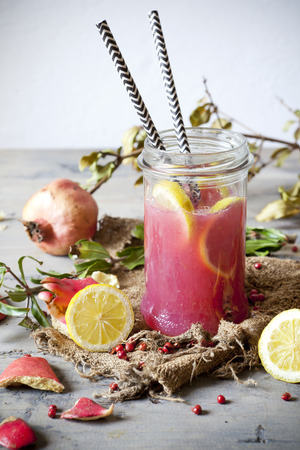 pink  leaf: pomegranate and lemon smoothie on glass jar with two striped straw on rustic background with lemon slices and burlap