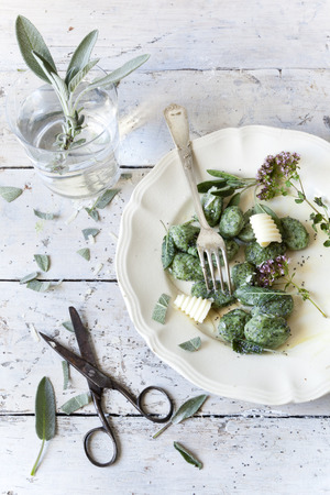 prepared potato: homemade spinach dumplings with sage leafs, butter curls, flowers on plate on rustic background with vintage scissor