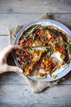 hand taking slice of homemade rustic pepperoni pizza on plate on vintage table photo