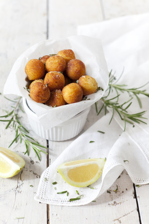 pomme: balls of fried potatoes on little bowl with lemon slice and rosemary on white background