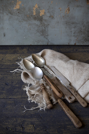 scraped: old used kitchen knives on frayed cloth on rustic scraped wooden table
