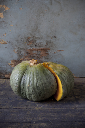 scraped: one pumpkin cut in half on rustic wooden table and scraped background Stock Photo