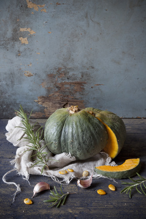 scraped: one pumpkin cut in half on rustic wooden table and scraped background with rosemary, garlic and cloth