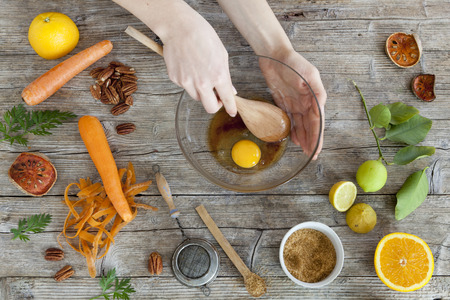 hands working on wooden kitchen table with raw ingredients and utensils photo
