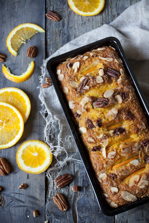 vegetable tin: citrus plumcake with pecan walnuts on mold on table with fresh orange slices Stock Photo