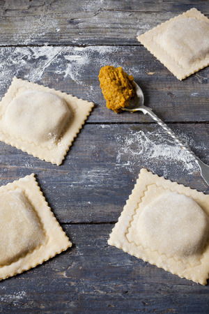 homemade stuffed with pumpkin ravioli big size on wooden table with flour and spoon photo