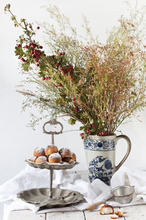 dessert stand: coconut sweets on vintage dessert stand with wild flowers bouquet on porcelain pitcher on white table