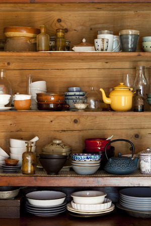ceramics and kitchen equipment on rustic and country style wooden shelves photo