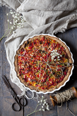 red peppers: baked red peppers tart on quiche mold on rustic table with cloth, scissor and spool