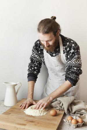 hombre con barba: hombre con estilo joven con barba en la cocina con el delantal que hace la pasta para la pasta con harina blanca y huevos a bordo de madera rústica Foto de archivo