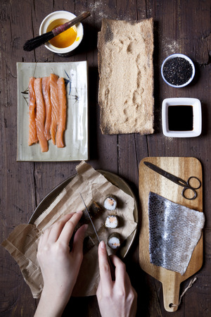 overhead shot of hands slicing a roll of hosomaki sushi and ingredients on table photo