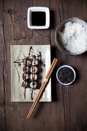 sushi roll: overhead shot of hosomaki sushi on plate with soy sauce and ingredients on table