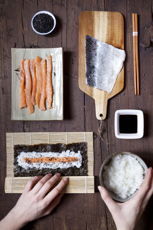 sushi: overhead shot of hands rolling sushi and ingredients on wooden table