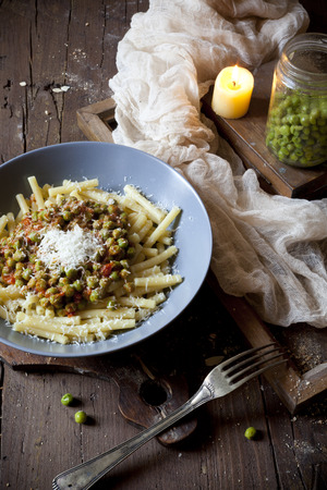 pastasciutta: pasta with tomato and whole peas sauce on plate with parmesan cheese on rustic wooden table