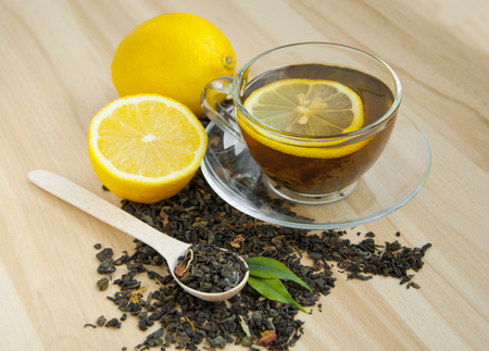 yellow  green: cup of tea with lemon over wooden background