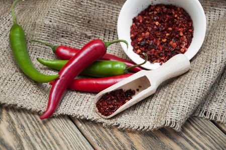 hottest: Green and red peppers on dark wooden  Stock Photo
