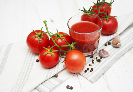 Fresh tomatoes and a glass full of tomato juice on a napkin photo