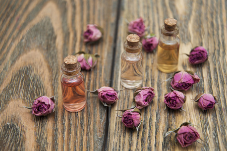 attar: Aromatic essences in small bottles and dry roses on wooden background