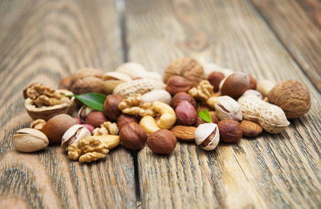 mixed nuts: Mixed nuts on a wooden background Stock Photo