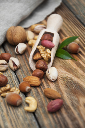 Mixed nuts in a spoon on a wooden background photo