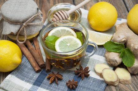 A cup of tea with fresh honey, lemon, ginger and spices on wooden background photo