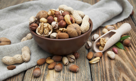 mixed nuts: Mixed nuts in a bowl on a wooden background Stock Photo