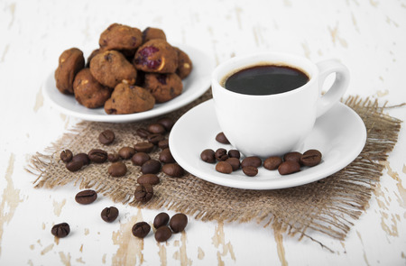 Cup of hot coffee and small cookies with spices on wooden background photo