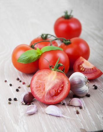 Ripe red tomatoes with spices on a wooden background photo