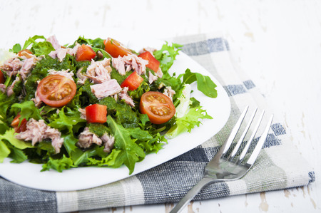 food  restaurant: Mixed salad with tuna and tomatoes on a wooden background Stock Photo