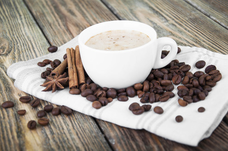 Cup of hot coffee with spices on wooden background photo