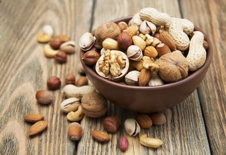 nuts: Mixed nuts in a bowl on a wooden background Stock Photo