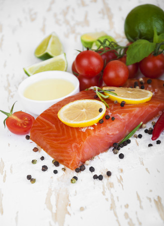 Portion of smoked salmon fillet with vegetables, aromatic spices and herbs on a wooden background photo