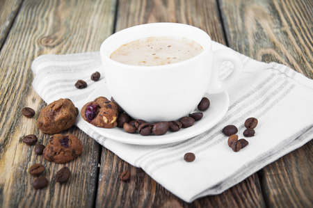Cup of hot coffee and small cookies on wooden background photo