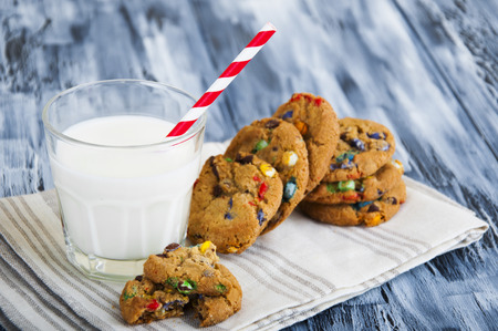 Glass, pitcher of milk and colorful oatmeal cookies on a wooden background photo