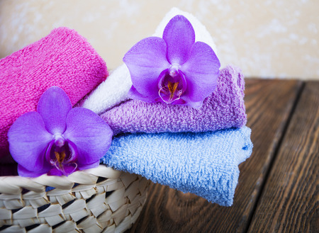 medium group of object: Bathroom soft and fresh towels folded in wicker basket with orchid on a wooden background