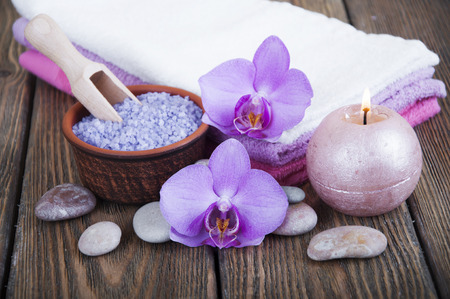 medium body: Spa composition with  spa accessories, orchid flowers and towels on a wooden background