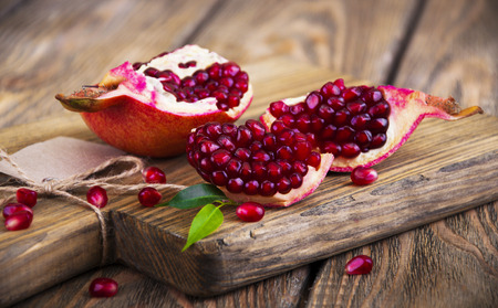 a pomegranate: Juicy pomegranate and red grains on wooden background